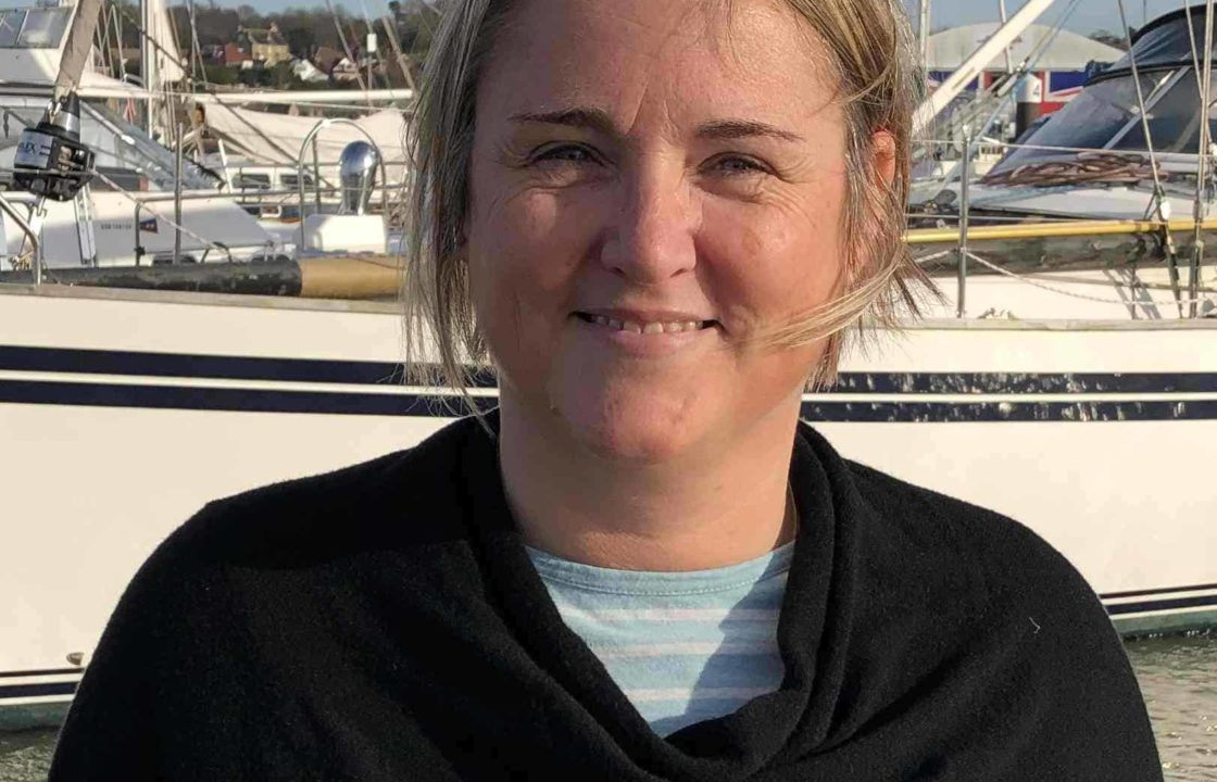 Minka Armitage, Halcyon Yachts Assistant Operations Manager, head and shoulders photo in front of a yacht.