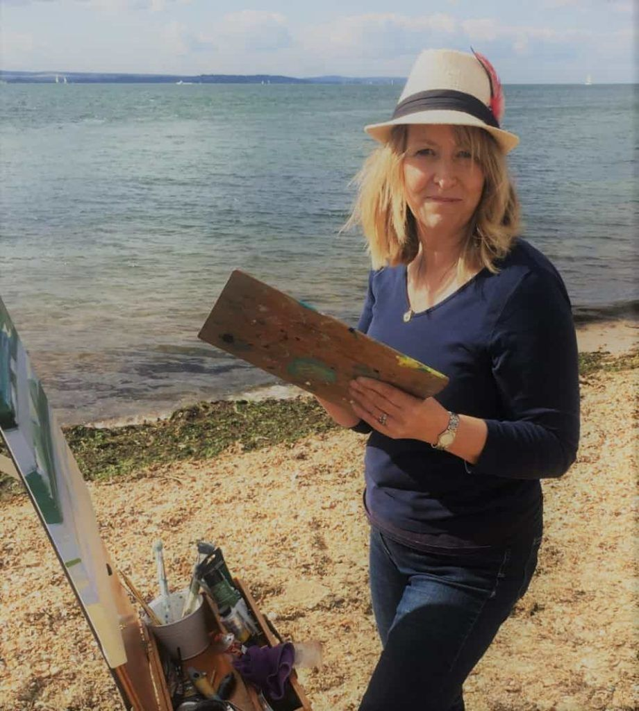 Artist Carolyn Tyrer standing by the sea and infront of her easel smiling and painting a picture