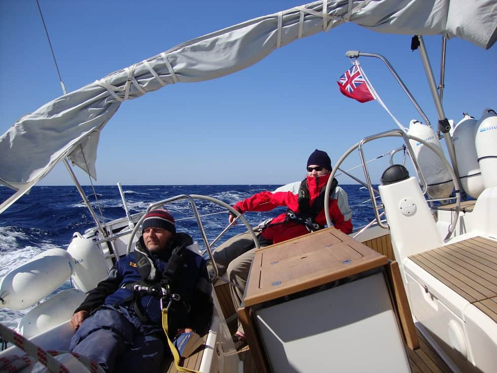 Two people sailing on a yacht delivery with wooly hats on!