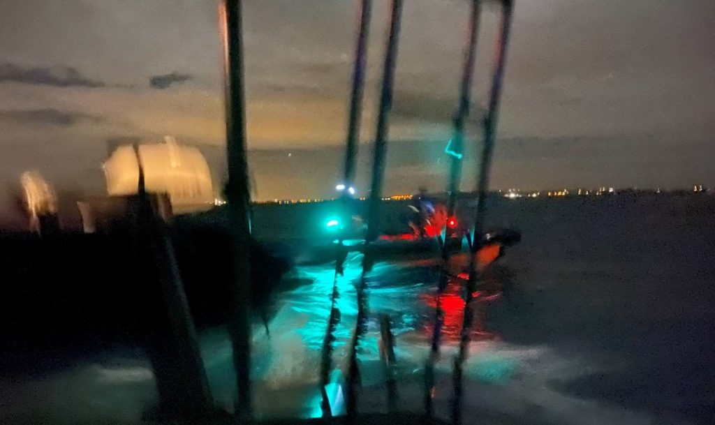A blurry picture of a police boat approaching us at night.