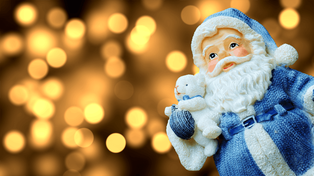 A model of Father Christmas holding a teddy bear.