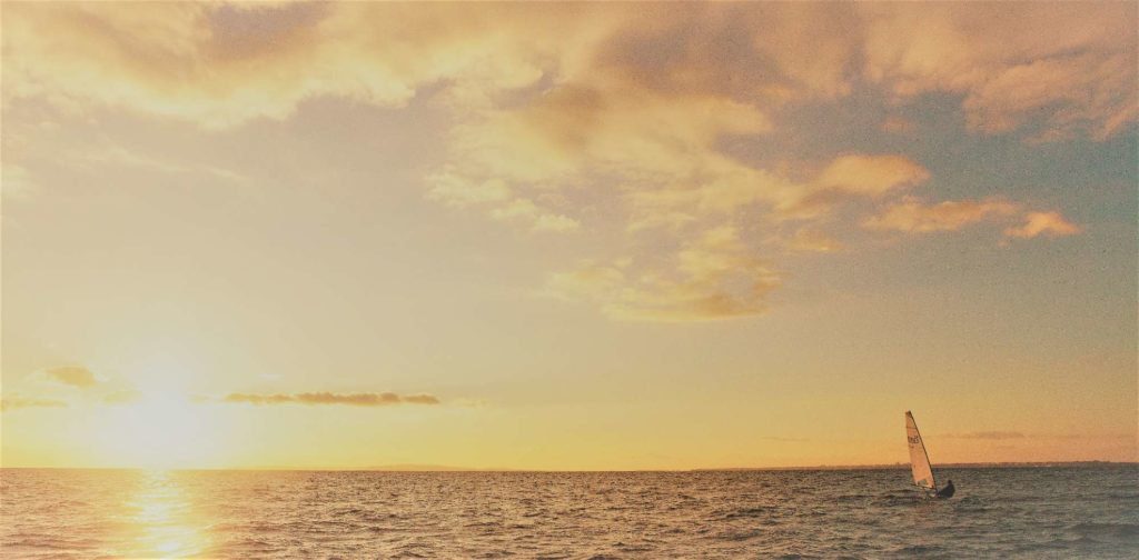 Sailing a dinghy in open water with the sun setting behind.