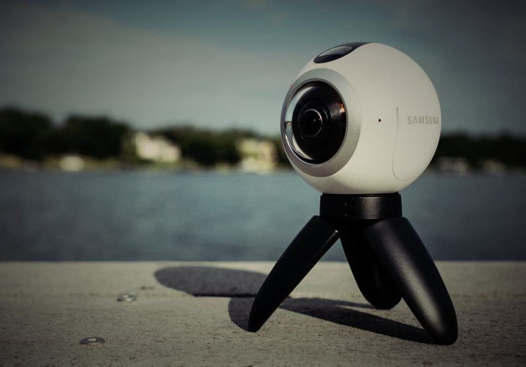 A samsung gear 360 camera close up with the sea in the background